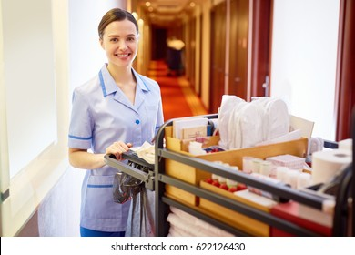 Young hotel staff bringing clean towels and other supplies
