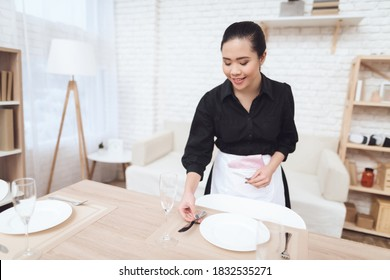 Young housekeeper arranges appliances on the table and smiles. Woman housekeeper lays down a knife near a plate while sets the table.