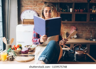 Young housewife in an apron reads recipe book