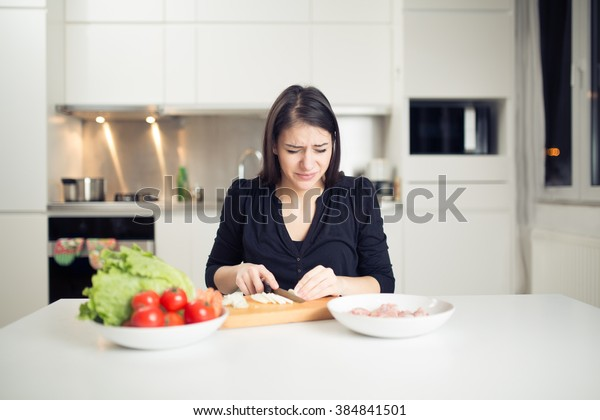 Young housewife beginner cook crying while cutting onion.Slice,dice and chop onion.Stinging eyes and tears when cutting onions to prepare dinner.Shedding tears and wiping with the back of her hand