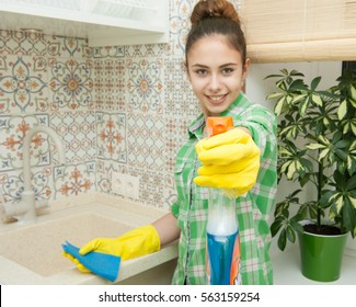 young housewife cleaning kitchen. woman pointing a spray bottle at the camera