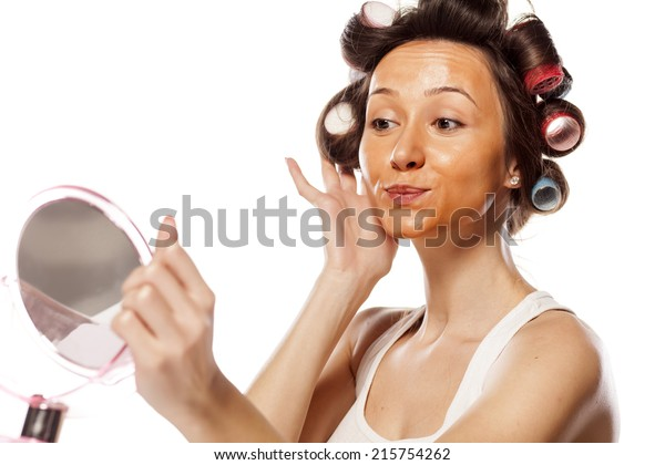 a young housewife with curlers and with wrong liquid foundation on her face