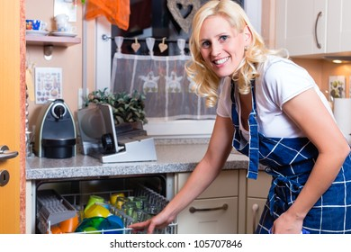 Young housewife is doing the dishes with dishwasher