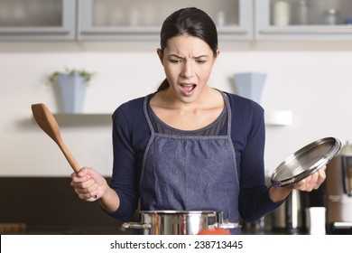 Young housewife having a calamity in the kitchen reacting in shock and horror as she lifts the lid on the saucepan on the stove to view the contents as she cooks dinner