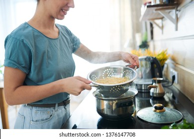 Young housewife with hot cooked spaghetti in colander standing by electric stove in the kitchen