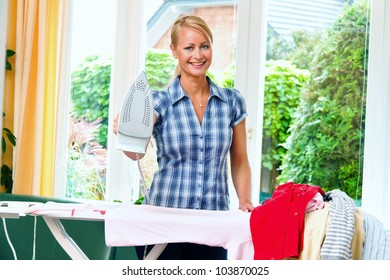 a young housewife with iron and ironing clothes.