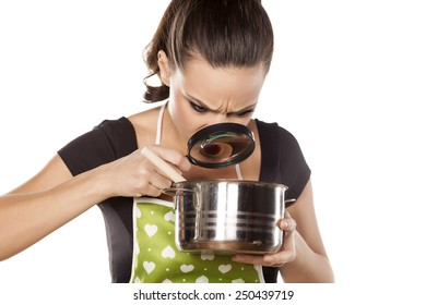 young housewife looking with a magnifying glass in a pan with food