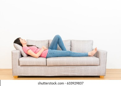 young housewife lying on couch and resting sleeping after completing house working at leisure time on wooden floor with white wall background.