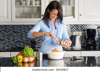 Young housewife preparing dinner out of a can