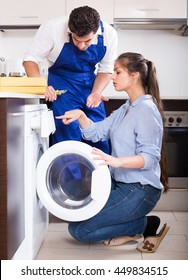 Young housewife and repairman near washing machine in domestic interior