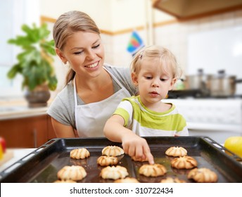 Young housewife with small child counting cooked biscuits on pan sitting at the table. Mother and daughter preparing pastry at home in the kitchen.