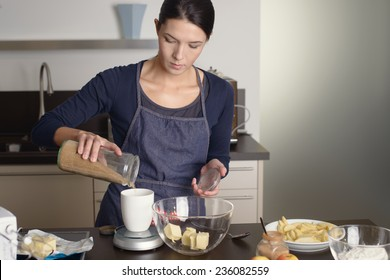 Young housewife standing at the counter in her apron baking in the kitchen pouring fresh ingredients into a kitchen scale weighing them to add to her mixing bowl and butter