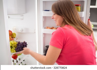 Young housewife take fresh sweet grapes from refrigerator