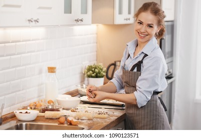 young housewife woman baking cookies at home in the kitchen