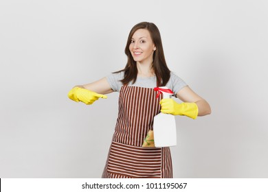Young housewife in yellow gloves, striped apron, cleaning rag in pocket isolated on white background. Woman holding and pointing on bottle with cleaner liquid, sponge. Copy space for advertisement