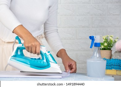 Young housewives who are using irons Ironing his clothes on a white brick background.