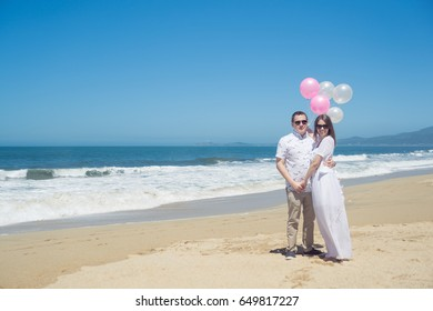 Young hugging romantic couple with balloons on the beach