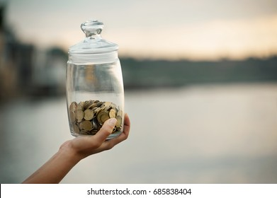 The young human hand is holding bottle money with money at the sunrise. Financial concept stability and well-being