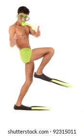 Young humorous Nepalese swimmer male in swimsuit with flippers, goggles and snorkel and with the foot bent in a knee pointing at camera. Studio shot. White background