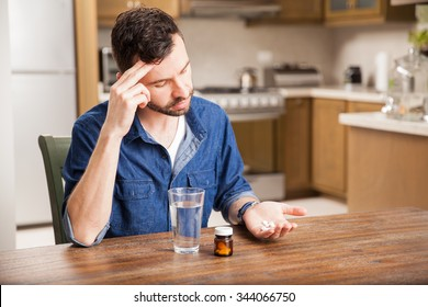 Young hungover man taking some pills to cure a headache at home