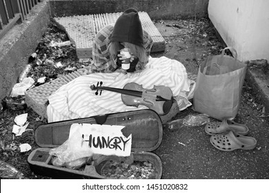 young hungry homeless woman begging on street