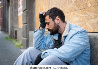 Young hungry unemployed sick depressed homeless homeless man sitting on the street in the city begging for money waiting to earn something to buy food to eat, social documentary concept