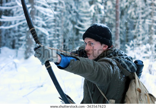 Young hunter with bow and arrows in the winter forest