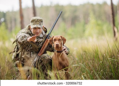 young hunter with a dog on the forest