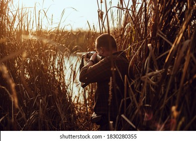 Young hunter man with a shotgun hiding in the reeds near the pond, at the duck hunt - photo with selective focus