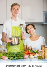 Young husband helping wife to prepare healthy dinner
