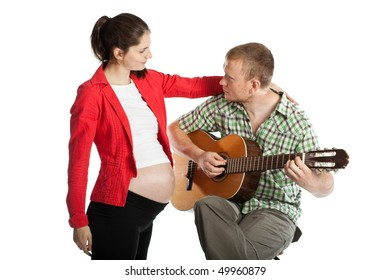 The young husband plays a guitar for the pregnant wife and the future child on a white background.