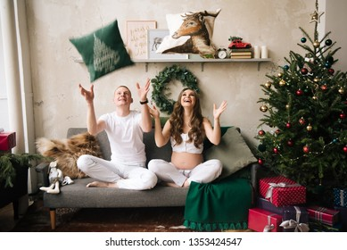 Young husband and pregnant wife in stylish home Christmas interior