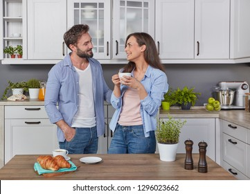 Young husband and wife drinking coffee in the kitchen