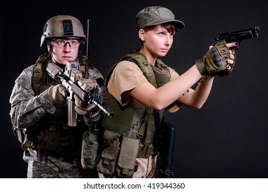 Young husband and wife in military uniform with guns on dark background/Family military squad