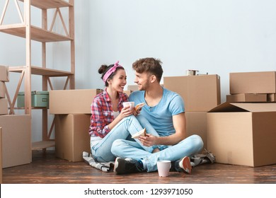 Young husband and wife moving to new place sitting on floor eating sandwiches drinking hot tea looking at each other talking laughing cheerful woman put legs on man.