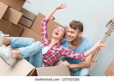 Young husband and wife moving to new place woman sitting in box hands up laughing playful closed eyes funny activity