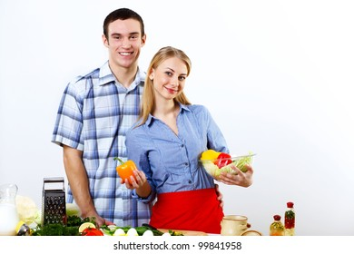 Young husband and wife together coooking at home