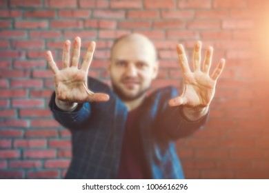 Young hypnotist or businessman in a jacket smiling and showing hands outstretched forward with palms, selective focus, toned