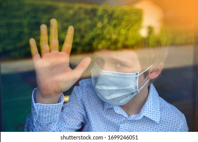 Young ill boy looking sad with protective mask at home behind window in quarantine and lockdown missing school and freedom during Covid-19 Coronavirus worldwide pandemic