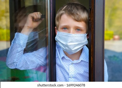 Young ill boy with protective mask at home opening window in quarantine and lockdown missing school and freedom during Covid-19 Coronavirus worldwide pandemic