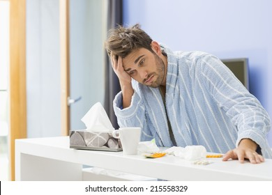 Young ill man with coffee mug; medicine and tissue leaning on kitchen counter