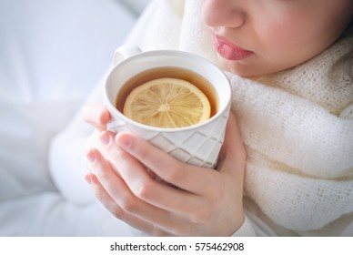 Young ill woman drinking hot tea with lemon at home, closeup