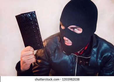 Young ill-intended man wearing black mask holds the black leather women purse and looks to his loot. Robber has stolen the wallet. Half shot of a thief in balaclava with a purse. Pickpocket affair