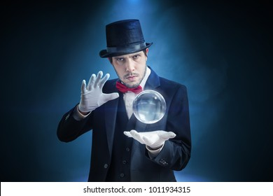 Young illusionist, magician or fortune teller is predicting future with crystal sphere.