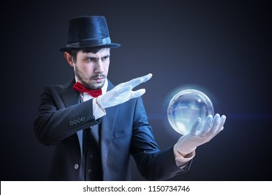 Young illusionist is predicting future and fortune telling from magical ball.
