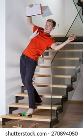 Young inattentive man slipping on stairs on a toy