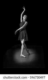 Young and incredibly beautiful ballerina is posing in darkness hall on parquet.