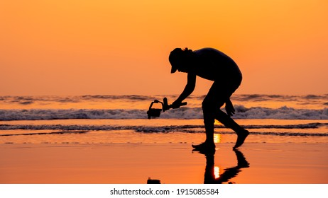 A young and independent filmmaker filming near beach silhouette