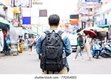 Young independent tourist man backpacker traveling alone in Khao San road market Bangkok Thailand on holidays