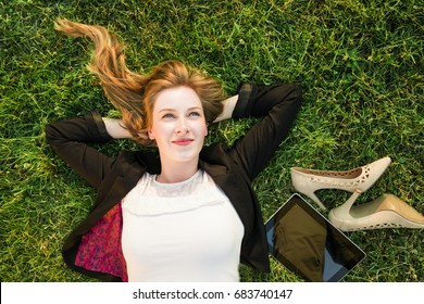young independent woman relaxing on grass in park